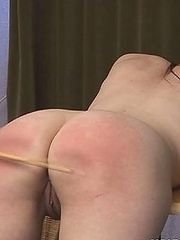 Naked girl bent over the table for brutal caning severe stripes